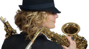 A woman with blonde hair holding a saxophone