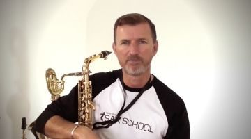 Nigel McGill holding his saxophone while sitting