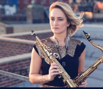 A blonde woman holding a saxophone